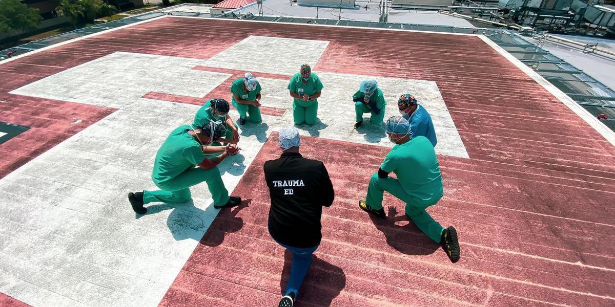 Nurses and doctors stand on hospital rooftops to pray over patients and families